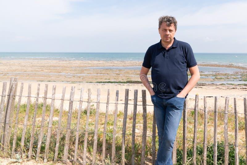 一个英俊的微笑的人的画象蓝色马球身分的在海滩在Isle de Re法国在网横幅模板网 免版税库存照片