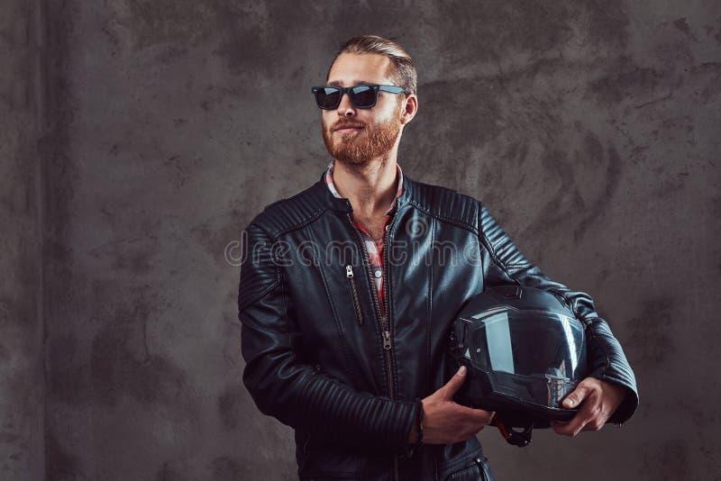 一个英俊的时髦的红头发人骑自行车的人的画象黑皮夹克和太阳镜的,举行摩托车盔甲,摆在 免版税图库摄影