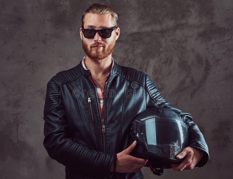 一个英俊的时髦的红头发人骑自行车的人的画象黑皮夹克和太阳镜的,举行摩托车盔甲,摆在 库存照片