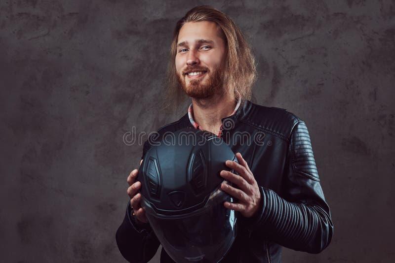 一个英俊的时髦的红头发人骑自行车的人的画象黑皮夹克的,举行摩托车盔甲,摆在演播室 库存照片