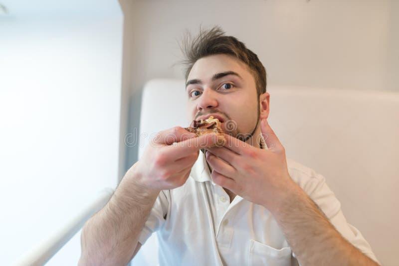 一个英俊的有胡子的人吃一个开胃薄饼并且看照相机 午餐的薄饼 免版税图库摄影