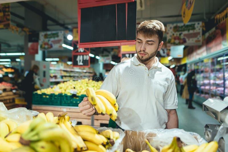 一个英俊的有胡子的人在超级市场买香蕉 一个人选择在菜部门的果子 免版税库存图片