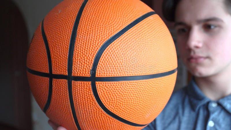 一个英俊的男孩少年拿着一basketballl 免版税库存照片
