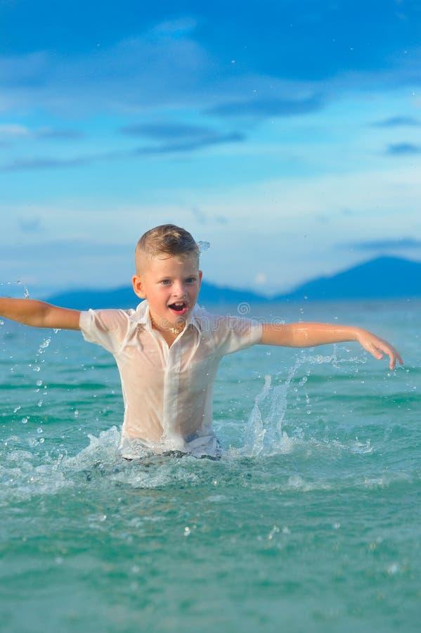 一个英俊的男孩的特写镜头画象湿微小的适合衬衣的跳过并且振翼水,很多飞溅和 库存照片