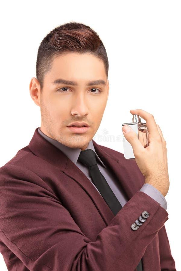 一个英俊的男性的画象在黑衣服的使用香水 免版税库存图片