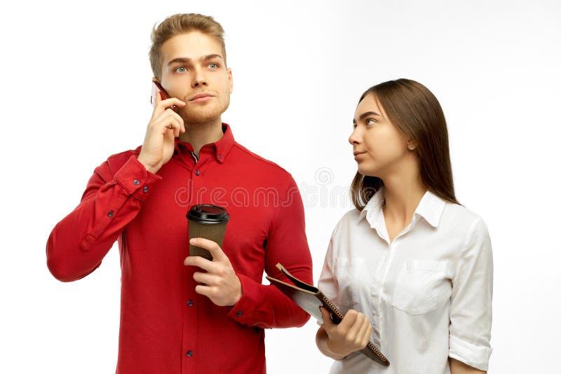 一个英俊的白肤金发的人困惑听在电话的上司 对秘书等待的指示不满意 免版税库存照片