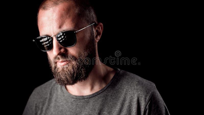 一个英俊的balded人的画象有长的好的被整理的胡子佩带的太阳镜和灰色衬衣的 库存图片