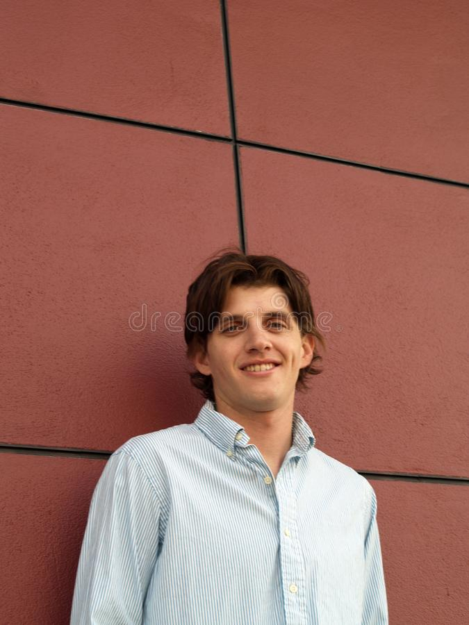 一个英俊的twentysome人的画象顶头射击有蓝眼睛的对有黑线的红色墙壁 免版税图库摄影