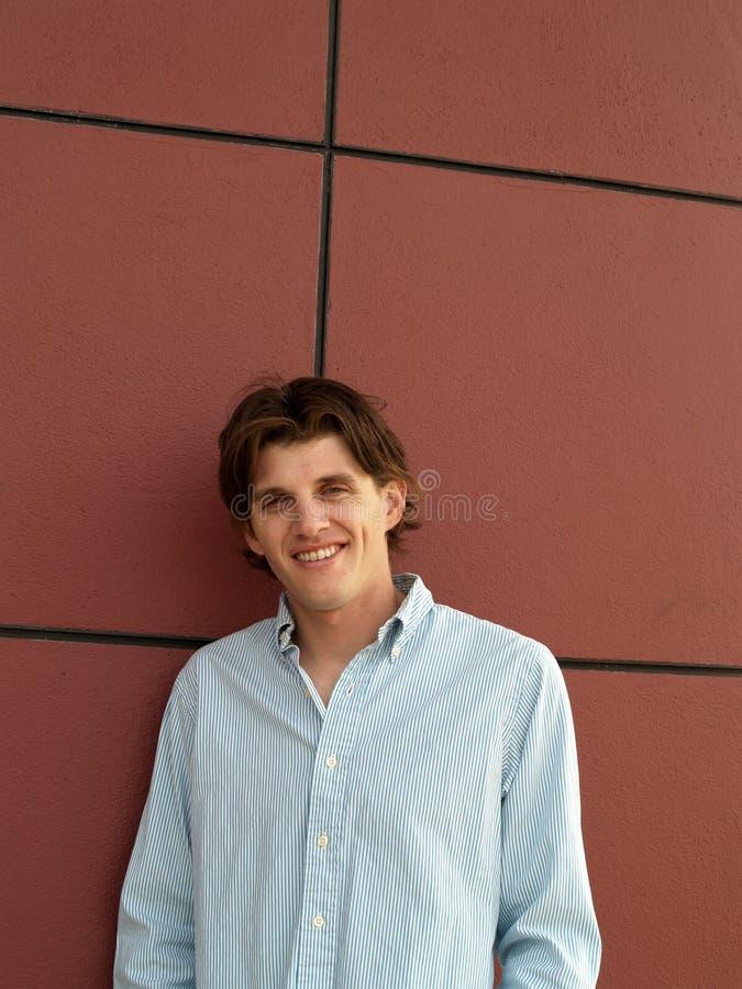 一个英俊的twentysome人的画象顶头射击有蓝眼睛的对有黑线的红色墙壁 库存照片