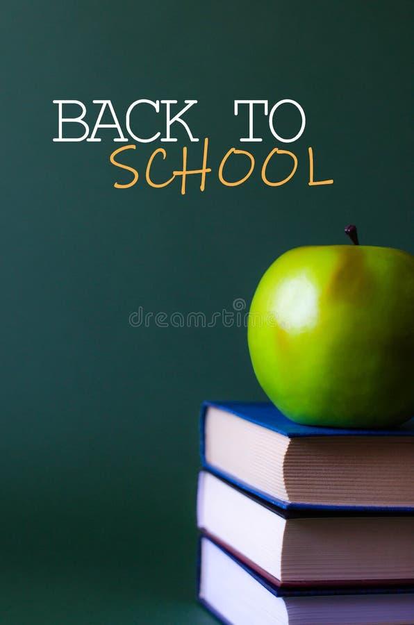 一个苹果在书和在回到学校的题字旁边 库存图片