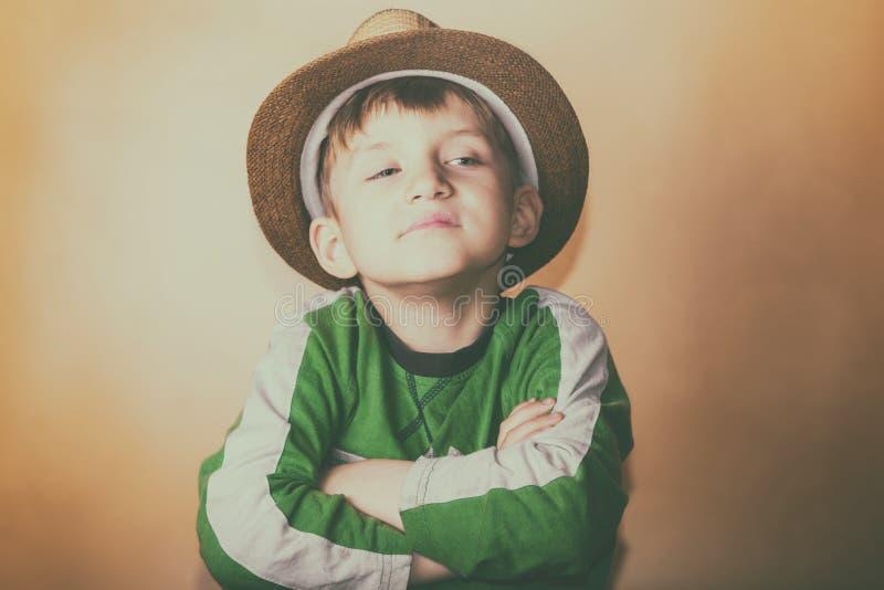 一个草帽的一个骄傲和贪婪的男孩有一个傲慢的表情的调查在黄色背景的照相机 免版税图库摄影