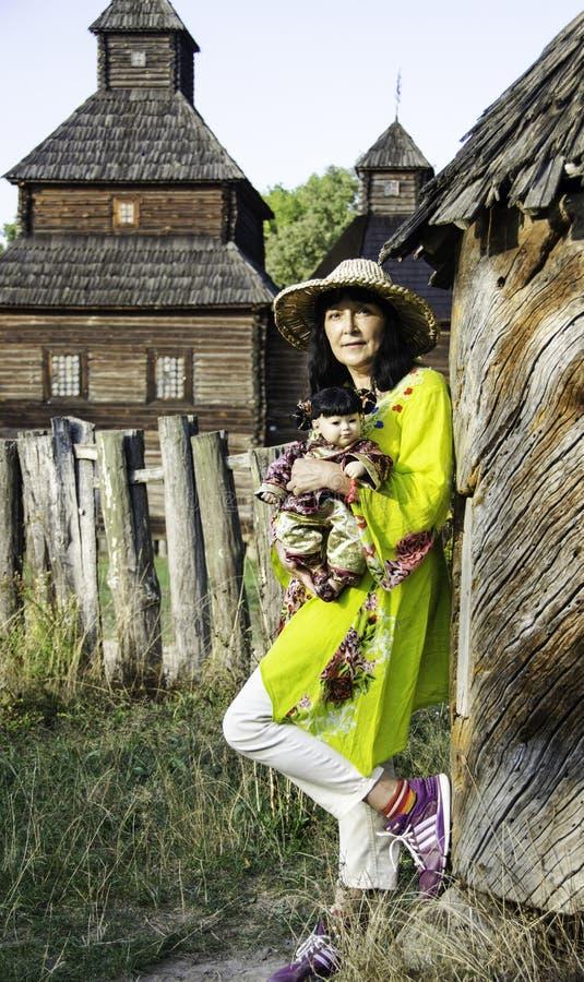 一个草帽的一名妇女有一个玩偶的在手上 图库摄影