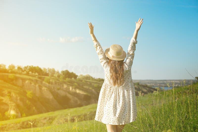 一个草帽的一名愉快的妇女有在山峭壁的边缘的顶部开放胳膊逗留的在日落光的下 库存图片
