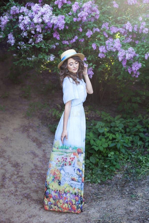 一个草帽的美女在一个淡紫色庭院里 有淡紫色花的女孩在春天 o 阴物,十的概念 免版税图库摄影