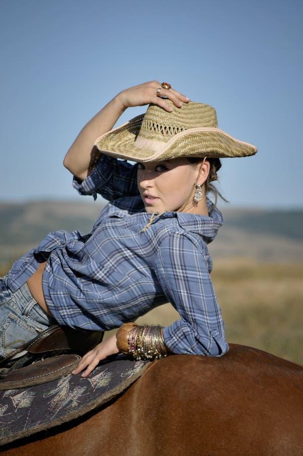 一个草帽的诱人的女牛仔在马 库存照片