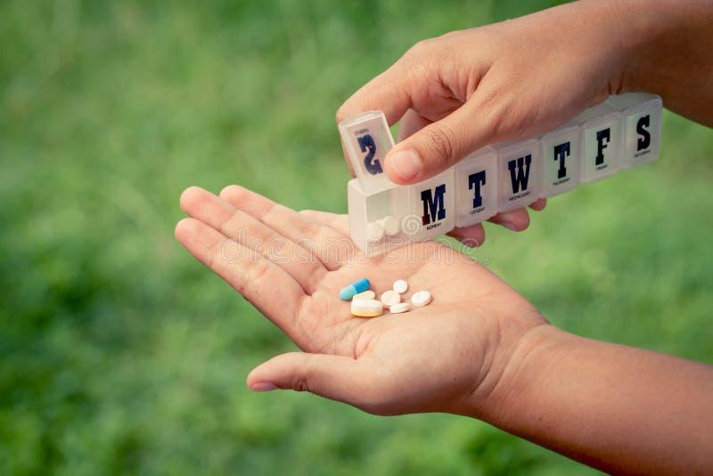 从一个药片提示箱子的妇女手倾吐的药片到她的手里 免版税库存图片