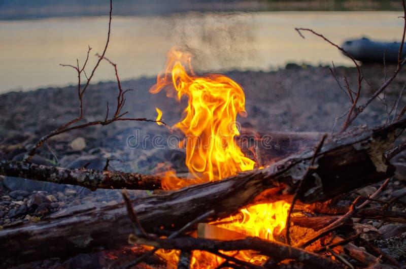 一个营火的火焰由河的 免版税库存图片