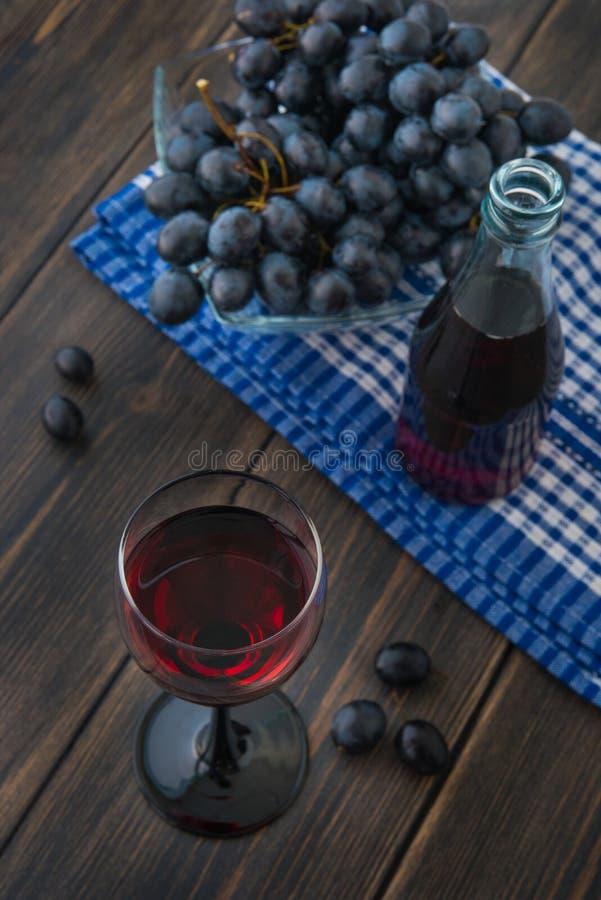 一个葡萄酒杯与玻璃瓶和bunc的年轻红色新鲜的酒 库存照片