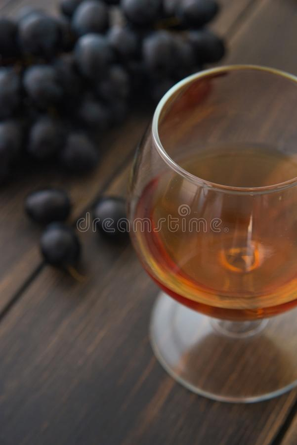 一个葡萄酒杯白兰地酒或科涅克白兰地与一束黑葡萄 库存照片