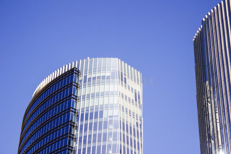 一个蓝色公司大厦的前面façade在它的双大厦旁边的 库存图片