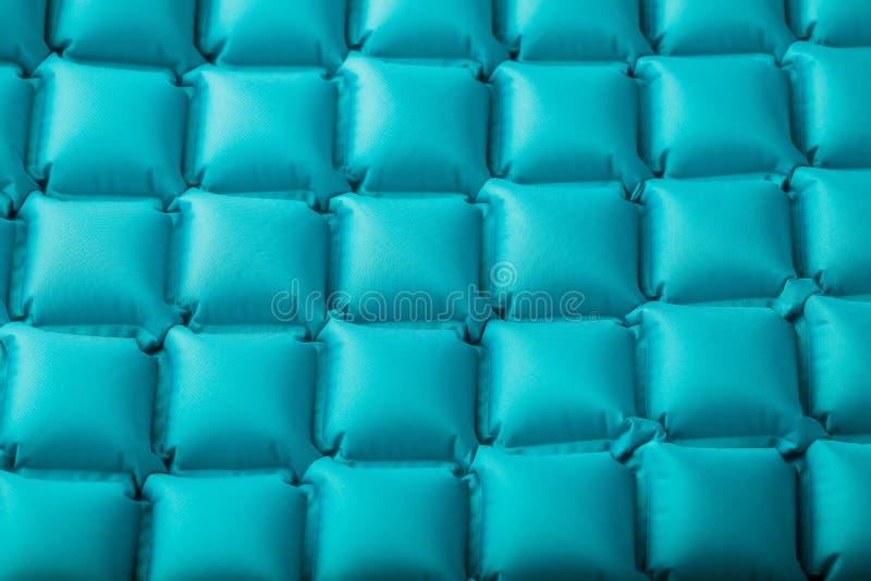 一个蓝色可膨胀的旅游地毯的纹理,重复部分和样式 气垫超轻型的便携式的地毯 库存图片