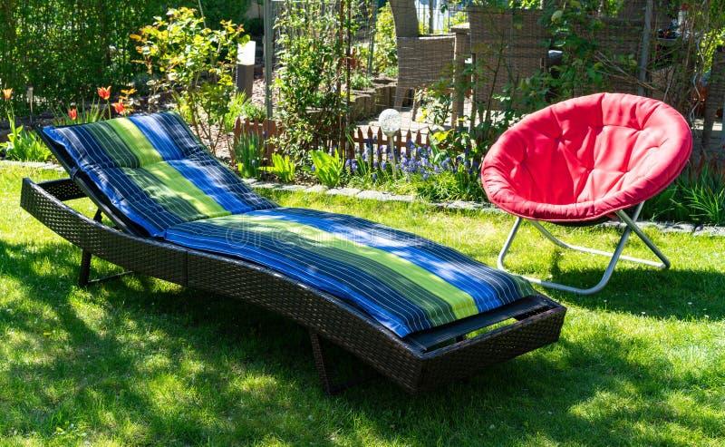 一个蓝色和绿色太阳懒人和一把红色折叠的月亮椅子在庭院里在阳光下 免版税库存照片