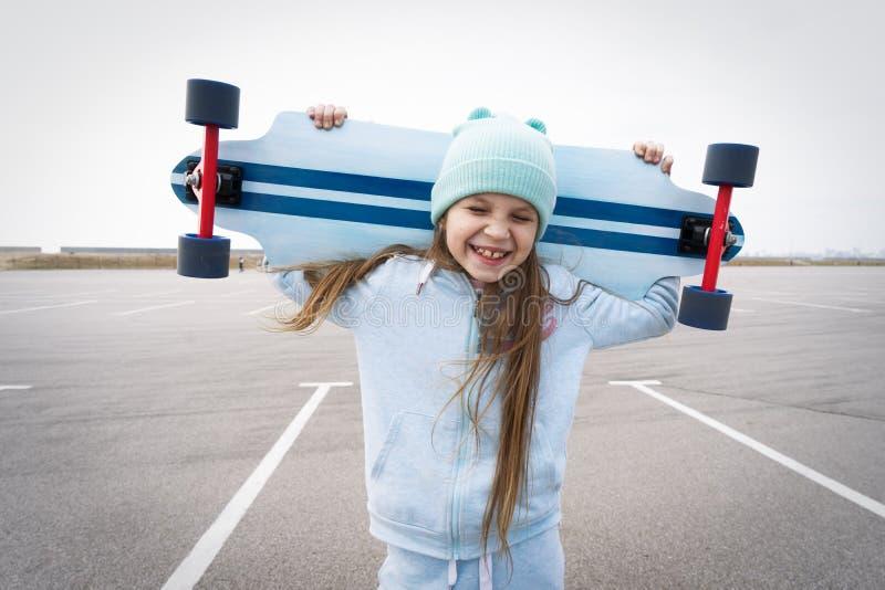 一个蓝色帽子的一个女孩愉快地举行在她的肩膀的一大longboard和笑与她的闭上的眼睛 库存图片