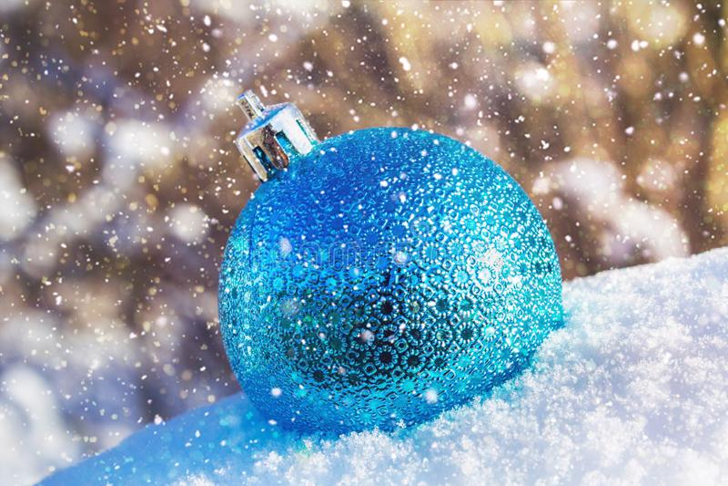 一个蓝色新年球在雪在 空白背景圣诞节玻璃查出的范围的玩具 免版税库存图片