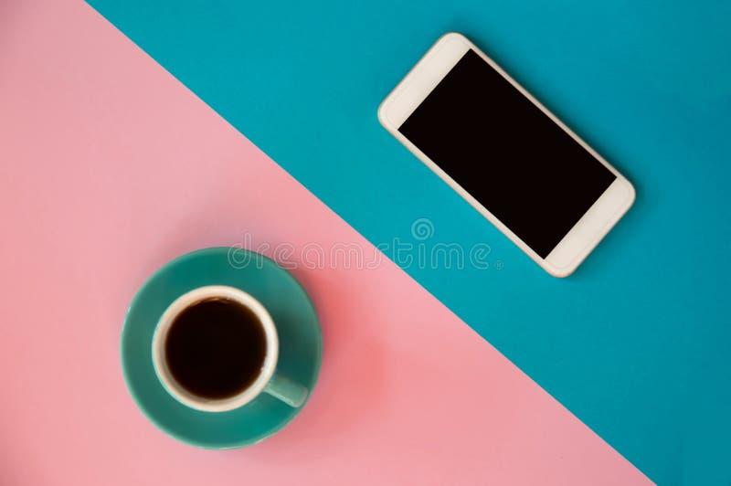 一个蓝色杯子用咖啡和一个手机在桃红色和蓝色背景站立 早晨早餐,事务 库存图片