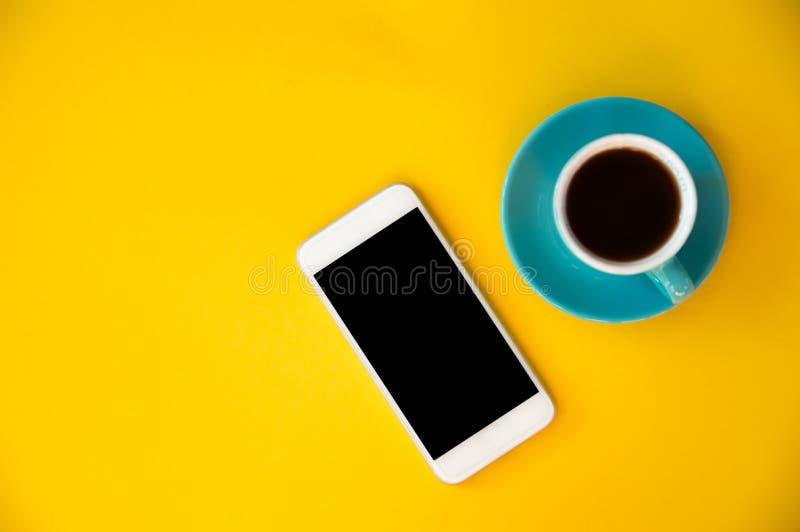 一个蓝色杯子用咖啡和一个手机在桃红色和蓝色背景站立 早晨早餐,事务 免版税库存照片