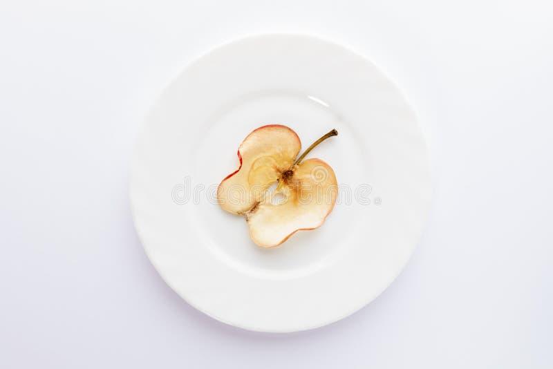 一个薄片在圆的白色板材的干苹果在白色背景 免版税库存图片