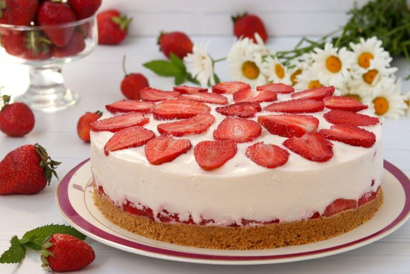 一个蛋糕用没有烘烤的草莓,与饼干基地,水平地在白色的一块板材被安置 免版税库存照片