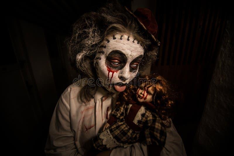 一个蠕动的女孩的画象有血淋淋的玩偶的 库存照片