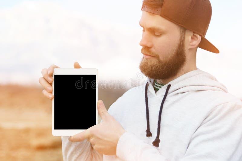 一个行家的特写镜头画象一个棕色盖帽的在他的手上露天拿着一台白色片剂个人计算机 一个有胡子的人神色 免版税库存照片
