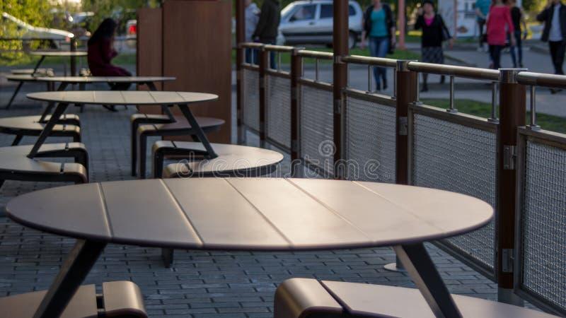 一个街道咖啡馆的空的桌在日落的在一个夏天晚上 免版税库存照片
