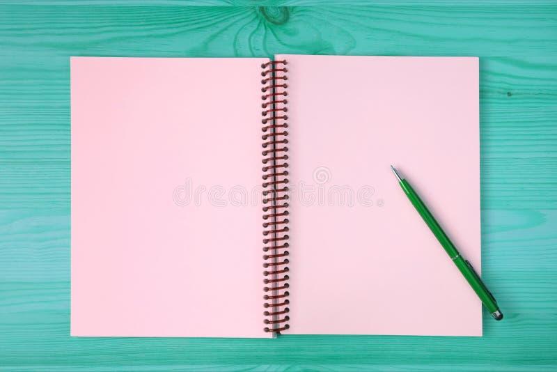 一个被打开的笔记本的桃红色空白页和在蓝绿色木桌上的一支绿色笔 免版税图库摄影