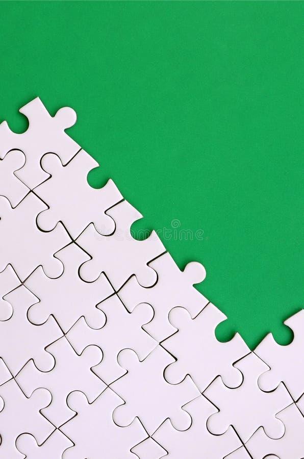 一个被折叠的白色七巧板的片段在绿色塑料表面的背景的 与拷贝空间的纹理照片文本的 库存照片