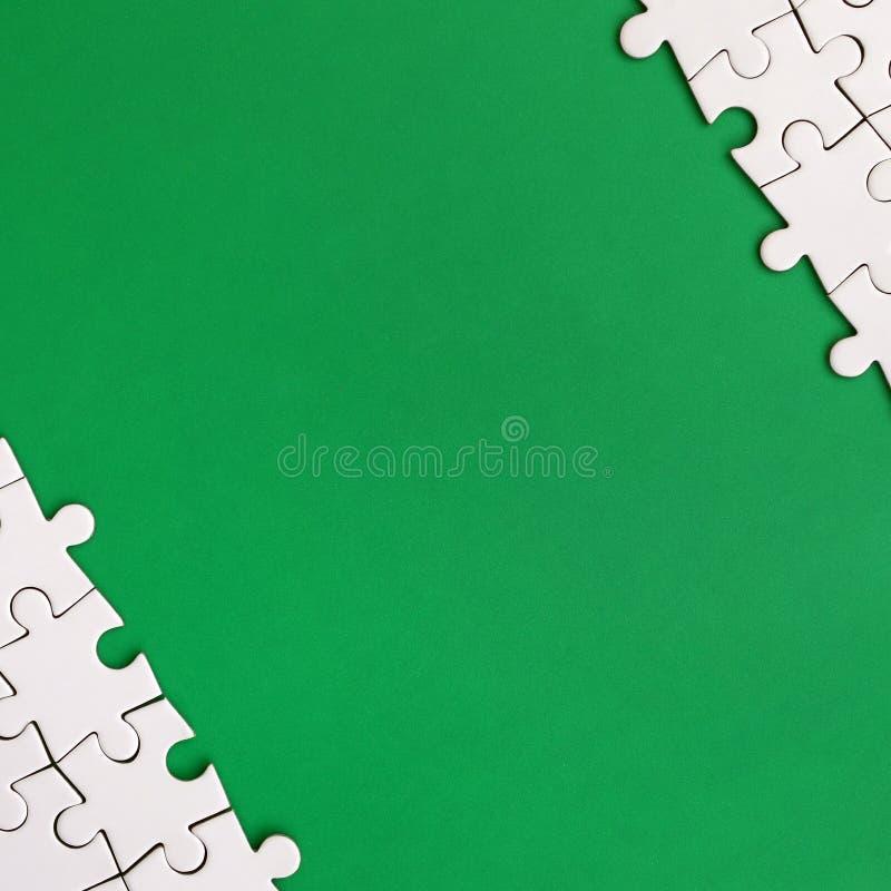 一个被折叠的白色七巧板的片段在绿色塑料表面的背景的 与拷贝空间的纹理照片文本的 皇族释放例证