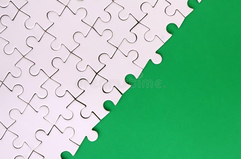 一个被折叠的白色七巧板的片段在绿色塑料表面的背景的 与拷贝空间的纹理照片文本的 库存图片