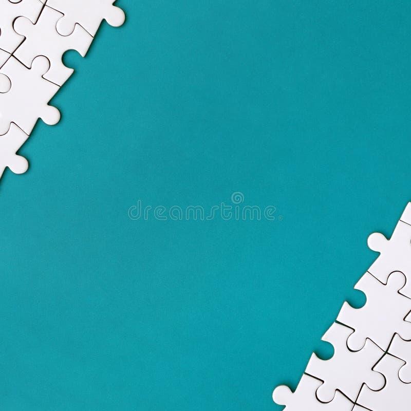 一个被折叠的白色七巧板的片段在蓝色塑料表面的背景的 与拷贝空间的纹理照片文本的 免版税库存照片