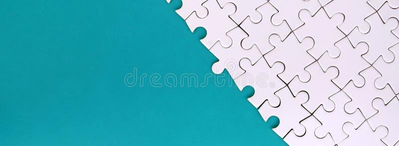 一个被折叠的白色七巧板的片段在蓝色塑料表面的背景的 与拷贝空间的纹理照片文本的 图库摄影