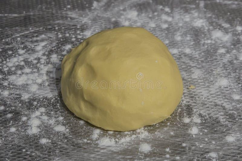 一个被撒粉于的金属表面上未加工的新鲜的曲奇饼面团的图象 免版税库存照片