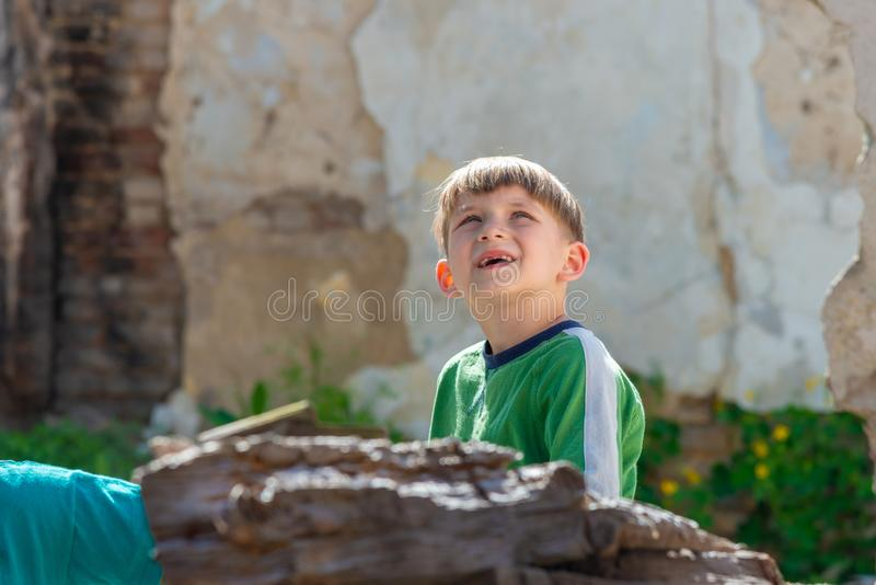 一个被放弃的和被毁坏的大厦的孩子在军事和军事冲突区域  社会问题的概念  免版税库存图片
