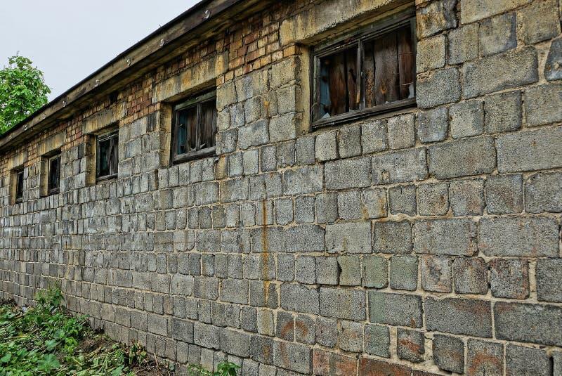 一个被放弃的大厦的灰色砖墙与残破的窗口的 免版税库存照片
