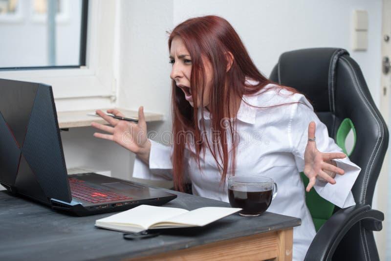 一个被注重的,恼怒的少妇坐在她的书桌并且是叫喊的在膝上型计算机以强烈的愤怒 免版税库存图片