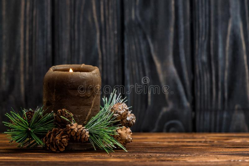 一个被点燃的棕色蜡烛用与小锥体的一个云杉的分支装饰 免版税库存照片