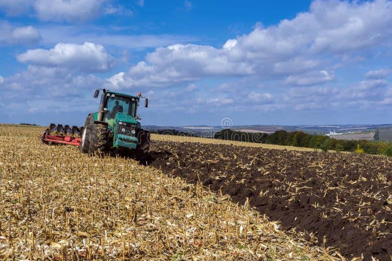 一个被犁的领域在收获与拖拉机完全机智的玉米以后 库存照片