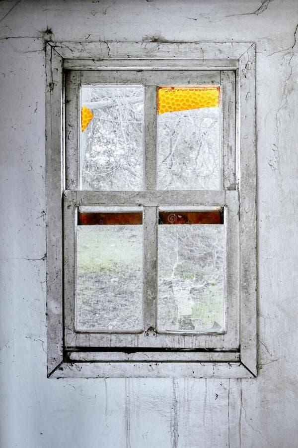 一个被破坏的房子的内部有老,肮脏和破裂的白色墙壁的和一个残破的窗架有一个绿色草甸领域视图 库存图片