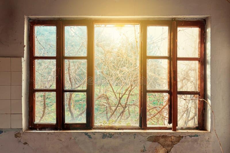 一个被破坏的房子的内部有老,肮脏和破裂的白色墙壁的和一个残破的窗架有一个绿色草甸领域视图 免版税库存照片
