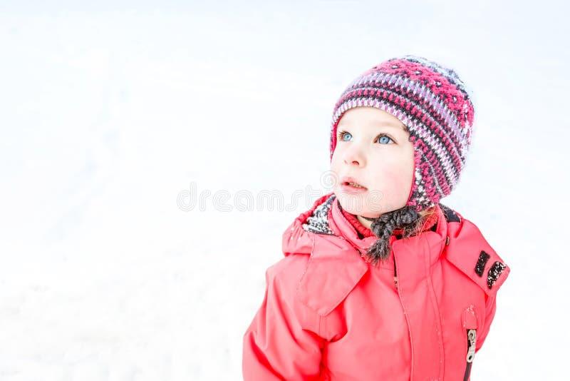 一个被编织的帽子和一件桃红色冬天夹克的一蓝眼睛的女孩查寻 背景路雪冬天 图库摄影